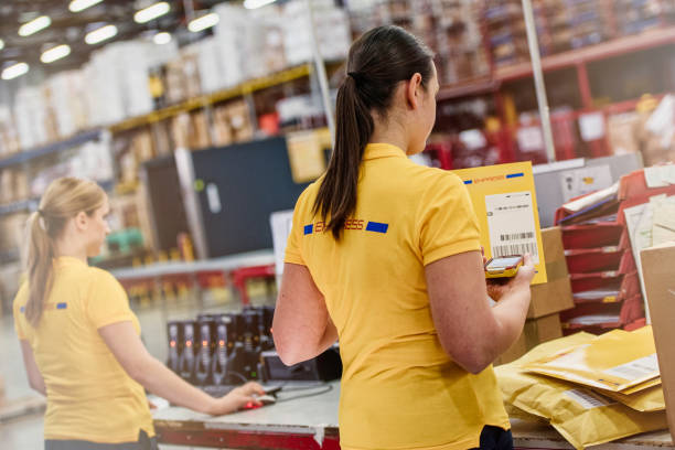 Rear view of two female warehouse workers checking mail.